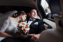 Young Couple In A Car In Wedding Day.