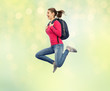 happy woman or student with backpack jumping