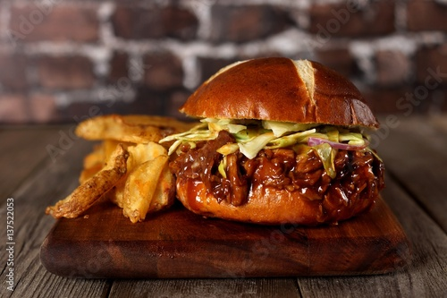 pulled pork burger on pretzel bun with potato wedges on a wood server with brick background. Black Bedroom Furniture Sets. Home Design Ideas