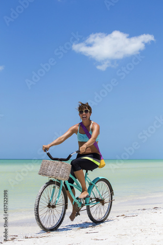 Fototapeta Woman rides bike to yoga at the beach obraz na płótnie