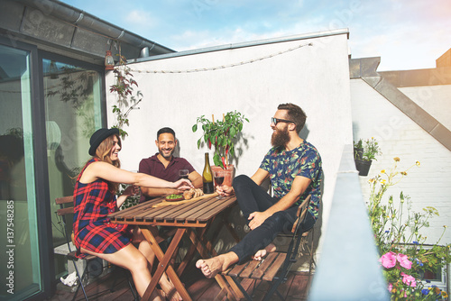 Fotografie, Obraz  Bearded man with couple drinking wine on roof