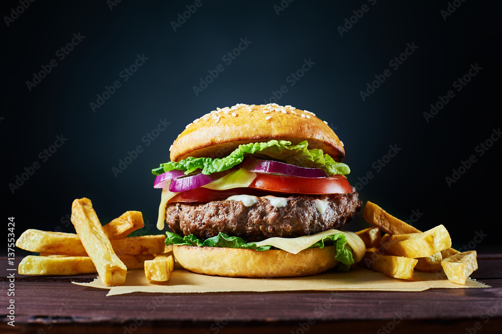 Fototapety, obrazy: Craft beef burger and french fries on wooden table isolated on dark background.