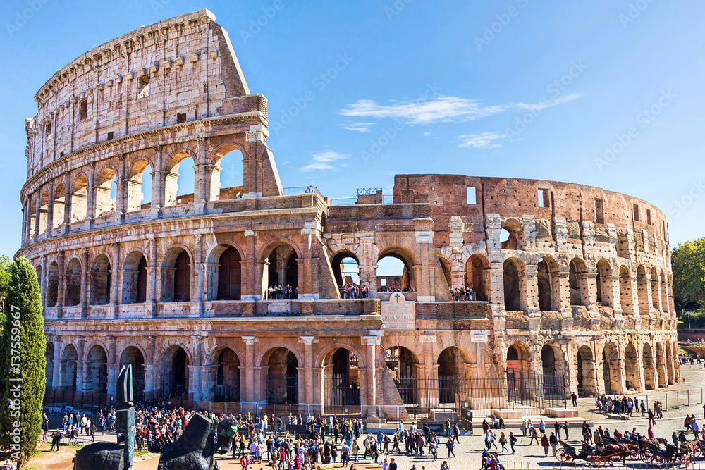 Valokuva  Ruins of the colosseum in Rome, walking visitors and tourists, sunny day with bl