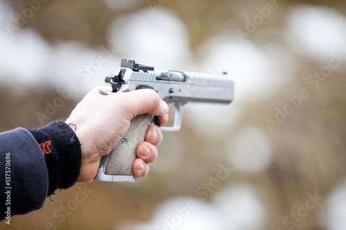 Arme de poing braquée et tir Fototapet