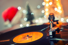 Image Of Christmas. Gramophone Playing A Record. Gramophone With A Vinyl Record On A Background Of Christmas Decorations, Cap, Christmas Tree And Bright Lights