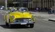 Auf der Hauptstrasse in Havanna Kuba fahrender amerikanischer gelber Cabriolet Oldtimer mit Touristen - Serie Kuba Reportage