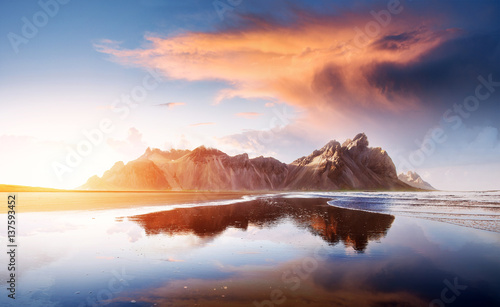 Fotobehang Noord Europa Amazing mountains reflected in the water at sunset. Stoksnes