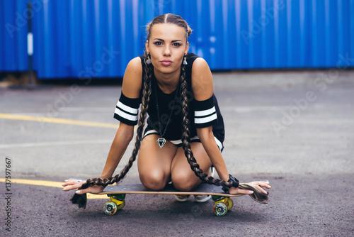 Fotografie, Obraz  Beautiful and sexy girl sitting on the skateboard