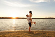 Happy honeymooners. Young couple embracing on sunset near sea or ocean