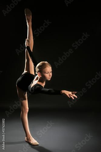 Poster de jardin Gymnastique Young girl doing gymnastic exercise on dark background