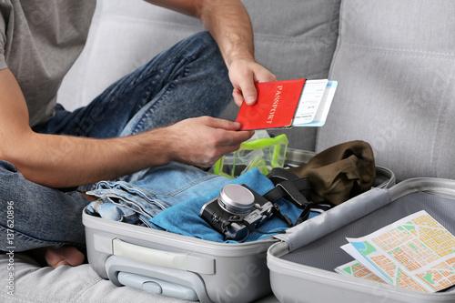 Fototapeta Man packing his grey suitcase in living room obraz na płótnie