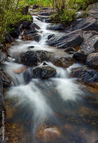 Fototapeten Forest river A portrait slow exposure river scene with large boulders and lush vegetation green in Vietnam.
