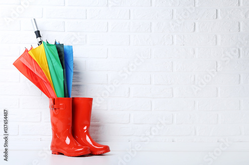 Fotografía  Red rubber boots with umbrella on brick wall background