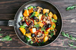 fried potatoes in a pan with tomatoes, mushrooms, olives, greens decorated with sprigs rosemary on a wooden table vegetarian food Top view