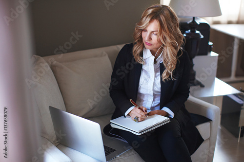 Fotografía  Business women working on coach with laptop in white and black suit