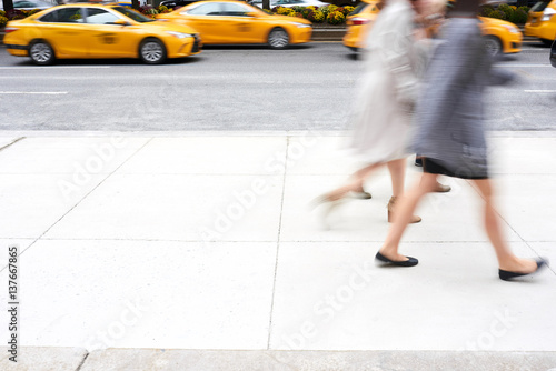 Foto op Plexiglas New York TAXI People walking in motion blur passing by yellow taxi cabs in Manhattan, New York