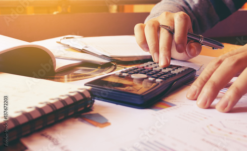 Fototapeta Woman using calculator with doing finance at home office. obraz