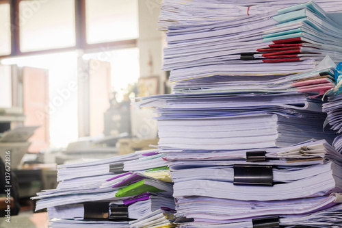 Valokuva  Pile of documents on desk stack up high waiting to be managed