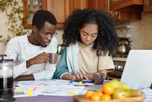 Finances And Family Budget Concept. Indoor Shot Of Serious African Girl Using Calculator While Paying Bills, Sitting At Kitchen Table With Papers And Notebook Pc, Doing Paperwork Together With Her Man