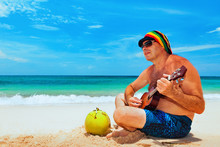 Happy Retired Age Man In Funny Hat Has Fun, Play Reggae Music On Hawaiian Guitar, Enjoy Caribbean Beach Party. Seniors Lifestyle And Leisure. Travel Family Activity On Jamaica Island Summer Holiday.