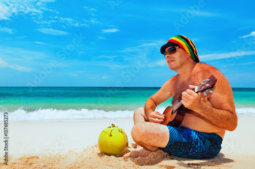 Foto  Happy retired age man in funny hat has fun, play reggae music on Hawaiian guitar, enjoy caribbean beach party