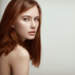 Beauty portrait of young beautiful sexy red-haired model with long straight hair.