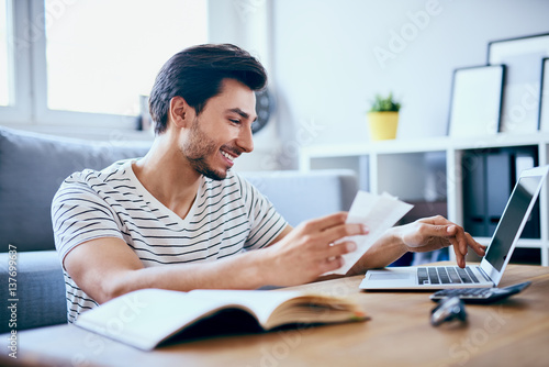 Valokuva  Happy man paying bills on his laptop in living room