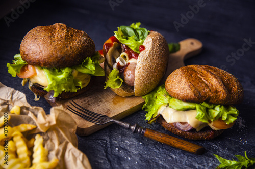 Fast food on the table: hot dog sausage and vegetables, burger with pork or beef and French fries with tomato sauce, basil leaves © lebedevaelena
