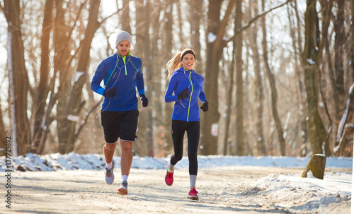 Poster Glisse hiver Couple in winter running together in nature
