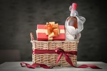 Wine Bottle With Gift Box In Wicker Basket On Dark Background
