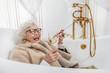 Leinwandbild Motiv Joyful mature lady relaxing in bathtub