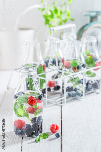 Staande foto Vlees Sparkling soda in bottle with berries and mint leaves