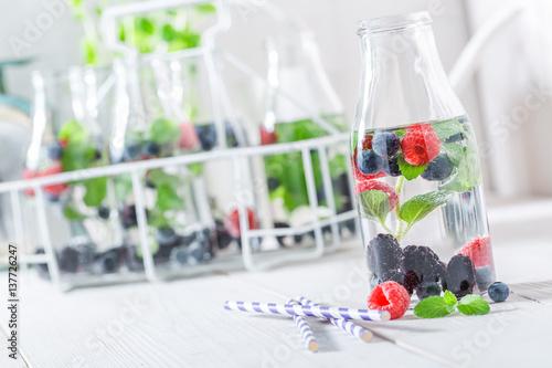 Staande foto Vlees Fruity soda in bottle with raspberries, blueberries and blackberries