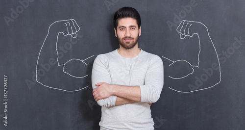 Young man against the background of depicted muscles on chalkboard Canvas Print