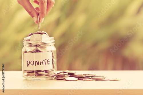 Fotografie, Obraz  Hand putting Coins in glass jar for giving and donation concept