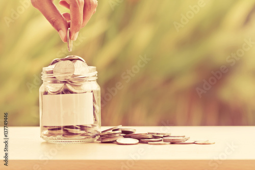Vászonkép Hand putting Coins in glass jar with blank label for giving and donation concept