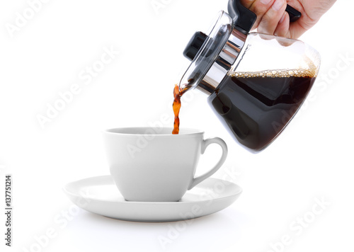 Foto auf AluDibond Kaffee Pouring coffee on a cup isolated on white background