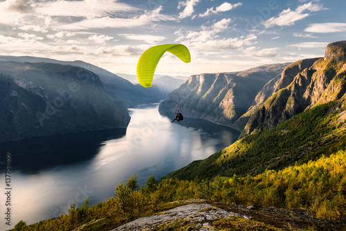 Foto op Plexiglas Luchtsport Paraglider silhouette flying over Aurlandfjord, Norway