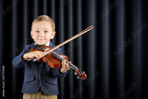 Plakat Chłopiec bawić się skrzypce na ciemnym zasłony tle
