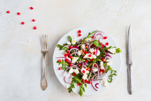 Dietary Salad With Red Onion, Arugula, Feta And Pomegranate Seeds In White Plate. Light Table, Top View.