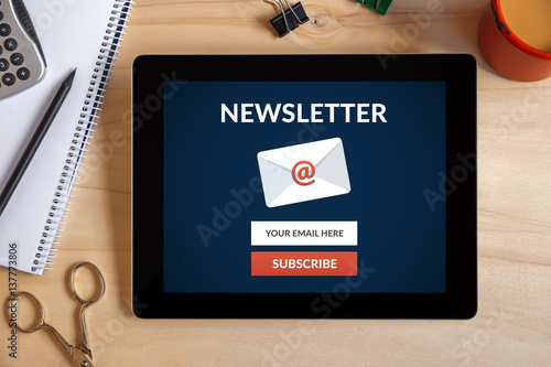 Fotografía  Subscribe newsletter concept on tablet screen with office objects on wooden desk
