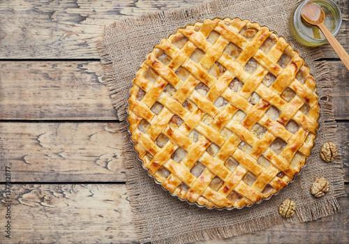 Photo  Apple pie tart with raisins, nuts and cinnamon on vintage wooden background texture