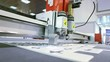 Computer controlled CNC cutting machine, cutting plastic foam, making small boxes form; close up, camera mounted at machine; slight vibrations;