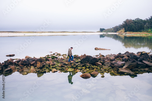 Man standing on rocks with sea around.