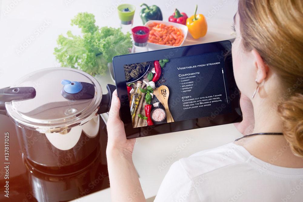 Fototapety, obrazy: Woman checks the recipe on her tablet.