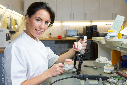Fotografie, Tablou  Dental technician holding articulator with prosthesis