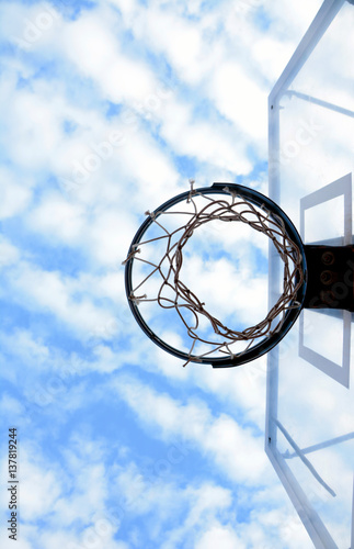 Fotografiet  Bottom view of basketball hoop and backboard with beautiful blue sky full of clouds in the background