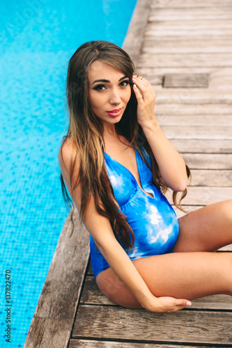 1fb322da0781e Beautiful pregnant woman relaxing near the blue pool in a swimsuit ...