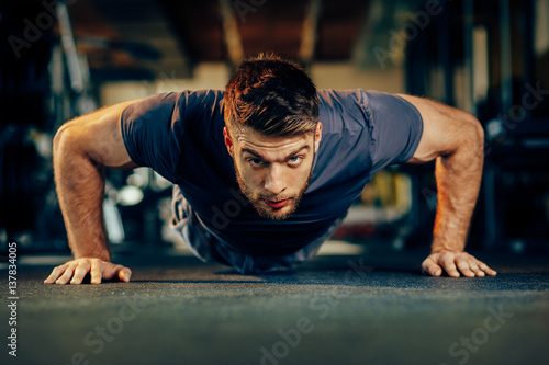 Fotografia  Handsome man doing pushups in the gym
