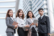 Team portrait of young confident and successful Asian business people smiling outdoor with cityscape in background